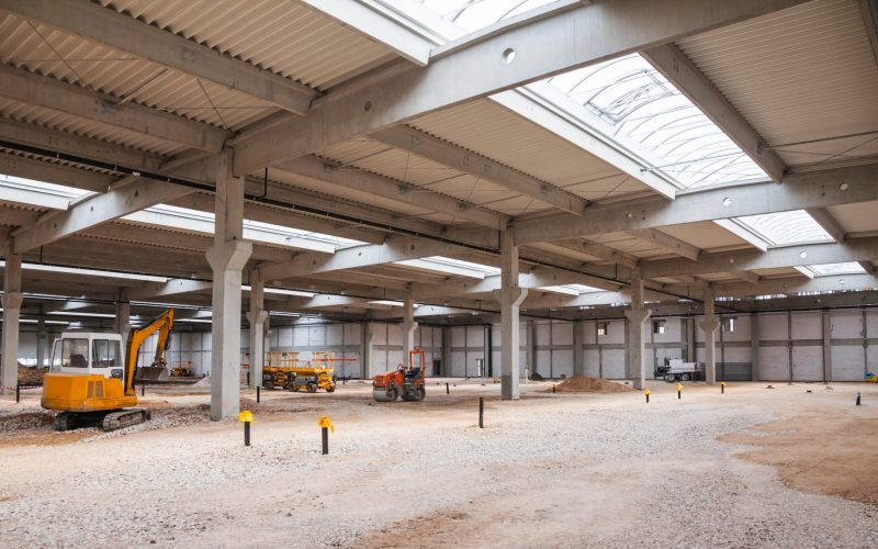 Industrial hall under construction with constuction machinery inside